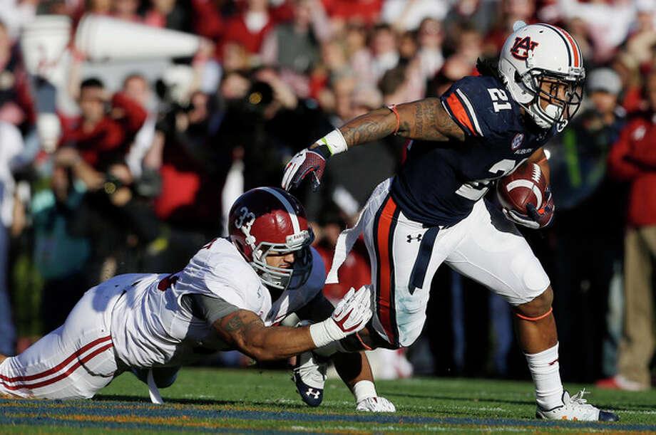 Auburn running back Tre Mason (21) is taken down by Alabama linebacker Trey DePriest (33) during the first half of an NCAA college football game in Auburn, Ala., Saturday, Nov. 30, 2013. (AP Photo/Jay Sailors) / FR171037 AP