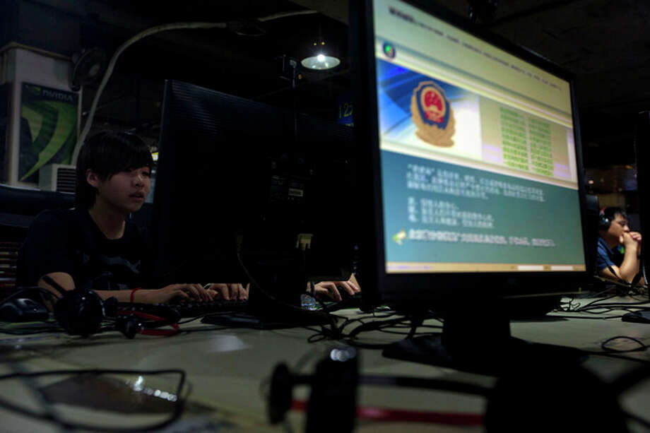 FILE - In this Monday, Aug. 19, 2013 file photo, computer users sit near a display with a message from the Chinese police on the proper use of the internet at an internet cafe in Beijing, China. The Chinese government has declared victory in its recent campaign to clean up what it considers rumors, negativity and unruliness from online discourse, while critics say the moves have suppressed criticism of the government and ruling Communist Party. (AP Photo/Ng Han Guan, File) / AP