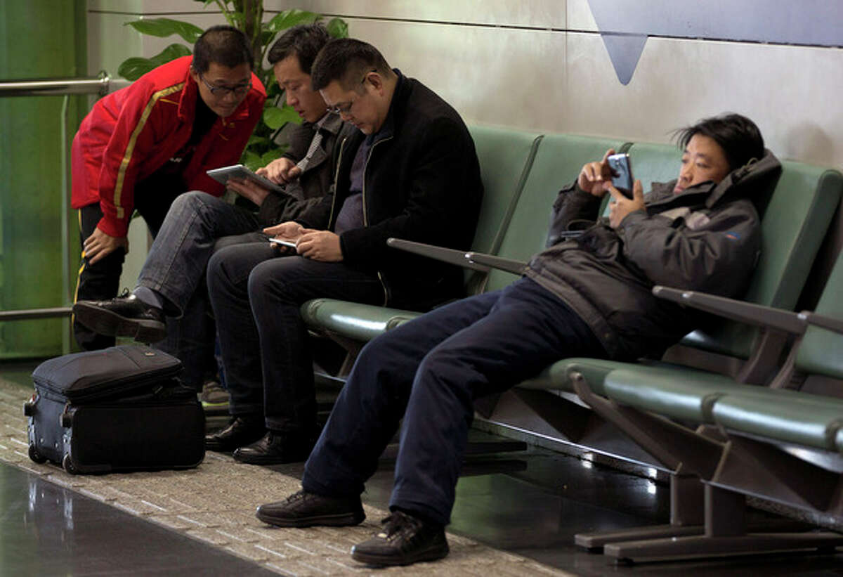 Men browse their tablet computers and smartphone at the Beijing Capital Airport in Beijing, China Saturday, Nov. 30, 2013. The Chinese government has declared victory in its recent campaign to clean up what it considers rumors, negativity and unruliness from online discourse, while critics say the moves have suppressed criticism of the government and ruling Communist Party. (AP Photo/Andy Wong)