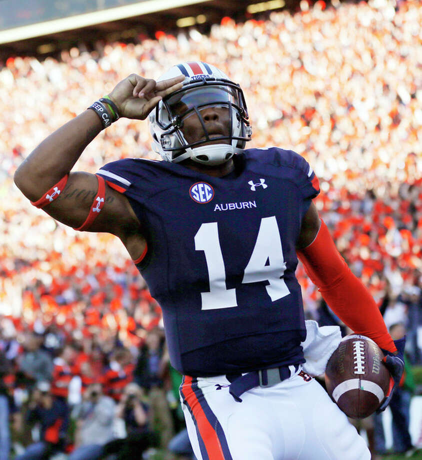 Auburn quarterback Nick Marshall (14) salutes after scoring against Alabama on a 45-yard touchdown run in the first half of an NCAA college football game in Auburn, Ala., Saturday, Nov. 30, 2013. (AP Photo/Dave Martin) / AP