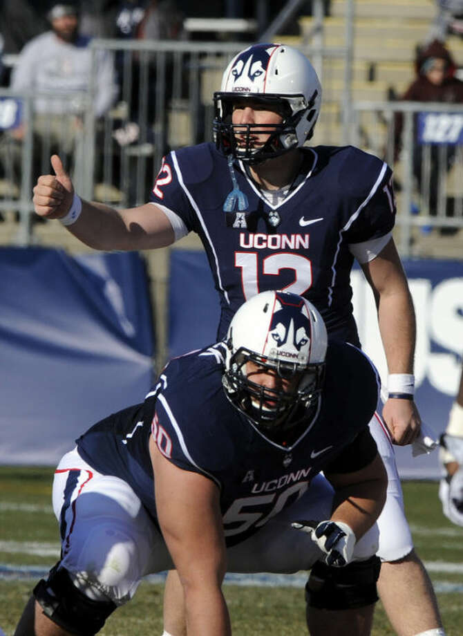 Connecticut quarterback Casey Cochran (12) signals while guard Tyler Bullock (50) looks on during the first half an NCAA college football game against Rutgers in East Hartford, Conn., on Saturday, Nov. 30, 2013. (AP Photo/Fred Beckham)