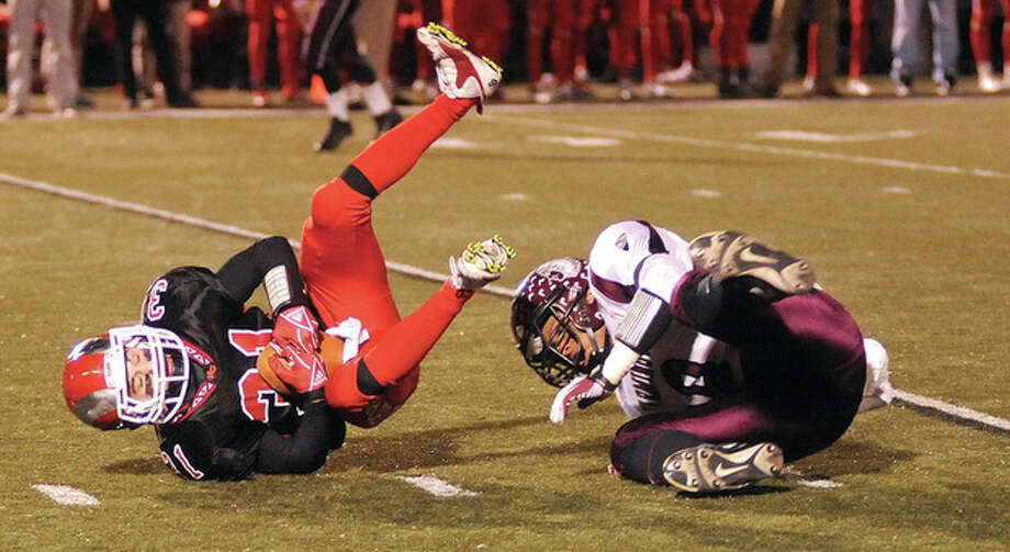 Hour photo/John NashNew Canaan's Michael DiCosmo, left, hangs on to the ball after getting upended by Farmington's Ivan Guadalupe on a second quarter reception during Tuesday night's Class L state playoff game. The Rams breezed to a 46-0 victory.