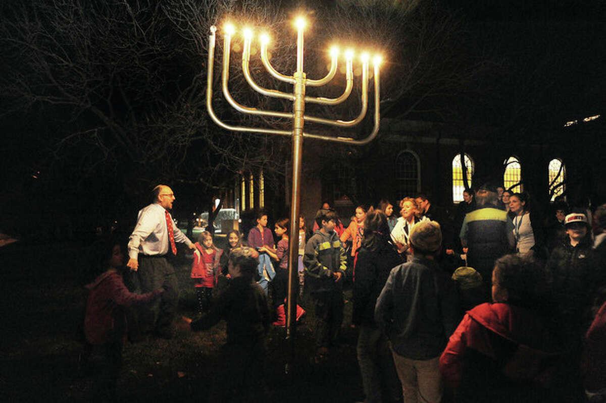 Rabbi Fish of Congregation Beth El leads a Hanukah lighting with children from Beth El's Nevasky Hebrew School on Tuesday night. Hour photo/Matthew Vinci