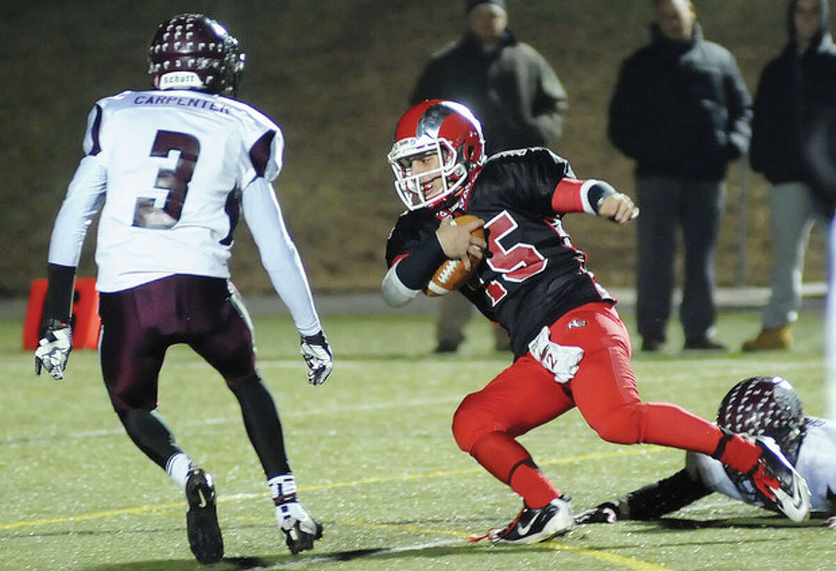 Hour photo/John Nash New Canaan quarterback Nick Cascione (15) slips away from a Farmington tackler as the Indians' Anthony Carpenter steps in to make the stop. Cascione and the Rams rebounded from their FCIAC championship game defeat by routing Farmington, 46-0.
