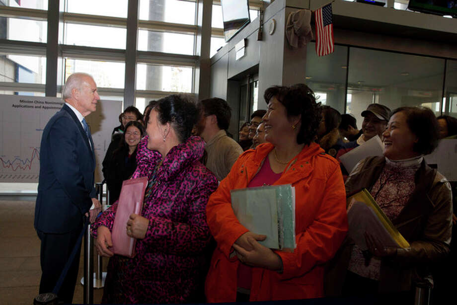 U.S. Vice President Joe Biden talks to visa applicants at the U.S. Embassy Consular Section in Beijing Wednesday, Dec. 4, 2013. (AP Photo/Ng Han Guan, Pool) / AP Pool