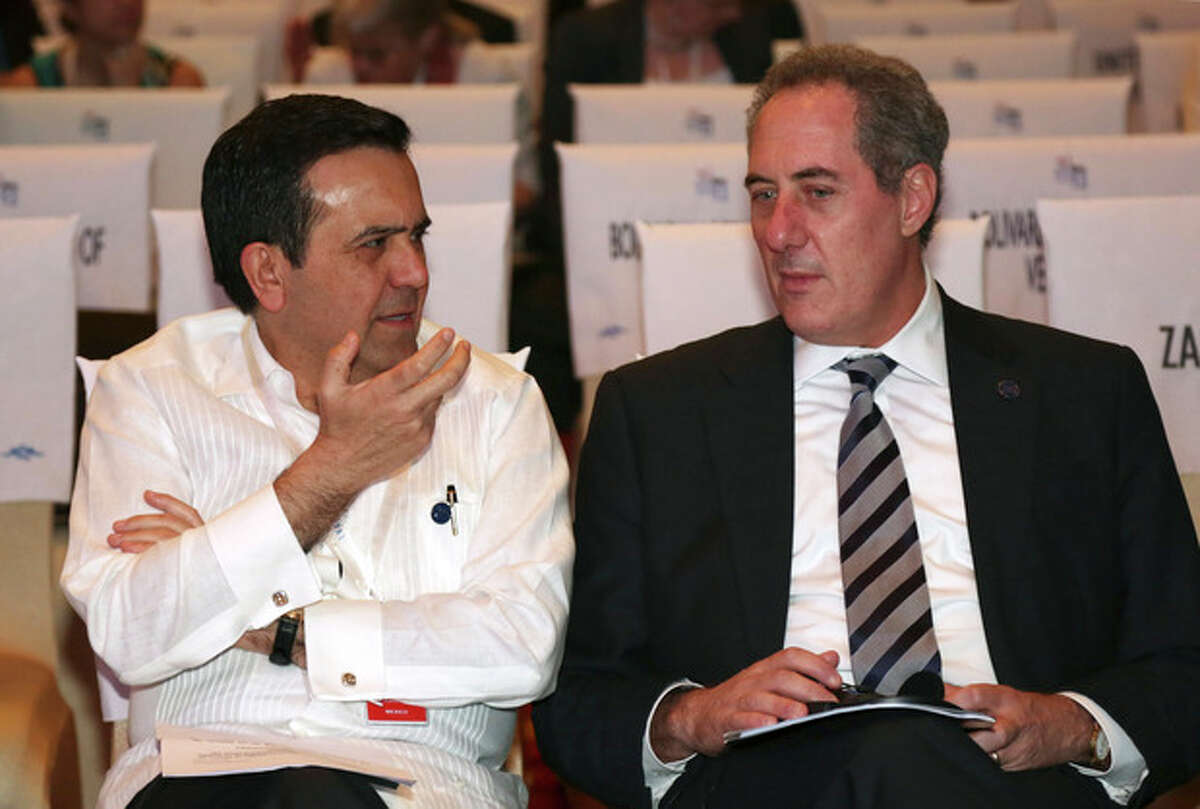 Mexican Economy Secretary Ildefonso Guajardo, left, talks with U.S. Trade Representative Michael Froman during the plenary session of the ninth Ministerial Conference of the World Trade Organization (WTO) in Bali, Indonesia, Wednesday Dec. 4, 2013. (AP Photo/Achmad Ibrahim)