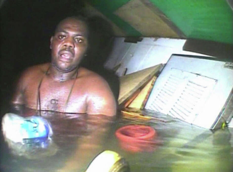 In this image made available Tuesday Dec. 3, 2013, Harrison Odjegba Okene looks in awe as a rescue diver surfaces into the air pocket which has kept Okene alive for nearly three days, recorded by the diver's headcam video the full impact of the miraculous encounter becomes plain the see. Okene was working as a cook aboard a tugboat in the Atlantic Ocean off the Nigerian coast in June 2013, when a heavy swell caused the vessel to capsize and his boat sank to the sea bed, where his 11 colleagues drowned, but Okene was able to find an air pocket inside the sunken ship where he survived for nearly three days before being found by a group of South African rescue divers. A video made available Tuesday Dec. 3, 2013, was filmed while the South African crew searched his vessel and found Okene alive before being given water and oxygen and then led to safety and to a decompression chamber for his recovery. (AP Photo/DCN Diving) / DCN Diving