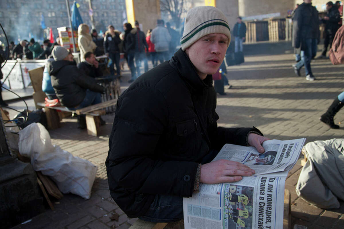 A protester reads a newspaper during a rally in Kiev, Ukraine, on Wednesday, Dec. 4, 2013. A resolution to Ukraine?'s political turmoil remained elusive as thousands of people continued rallying on Kiev?'s Independence Square and besieging key government buildings. (AP Photo/Ivan Sekretarev)