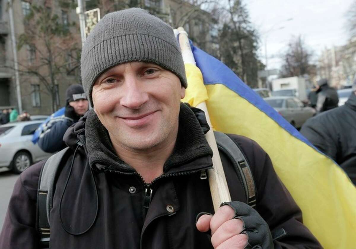 Leonid, a teacher from Lviv, holds a Ukrainian flag during a rally in downtown Kiev, Ukraine, Wednesday, Dec. 4, 2013. The Ukrainian government showed no sign of yielding Wednesday as thousands of people continued to rally in Kiev against the decision to freeze ties with the European Union and get closer to Russia. (AP Photo/Efrem Lukatsky)