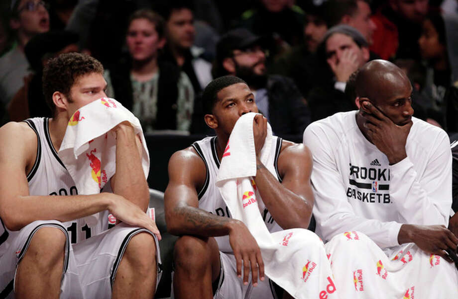 Brooklyn Nets forward Brook Lopez, left, guard Joe Johnson, center, and forward Kevin Garnett sit on the bench during the second half of an NBA basketball game against the Denver Nuggets, Tuesday, Dec. 3, 2013, in New York. The Nuggets won 111-87. (AP Photo/Kathy Willens) / AP