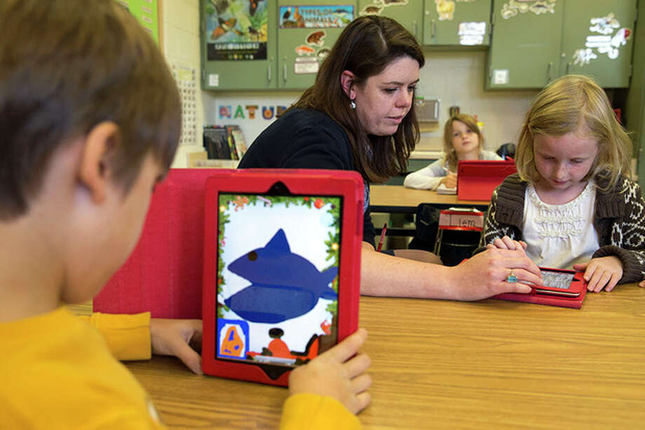 AP Photo / Jacquelyn MartinSecond grade teacher Heather Black working with Ingrid Soracco, 7, right, on her e-book assignment using an iPad at Jamestown Elementary School in Arlington, Va. Needed to keep a school building running these days: Water, electricity and broadband. Interactive digital learning on laptops and tablets is, in many cases, replacing traditional textbooks. Students are taking computer-based tests instead of fill-in-the bubble exams. Teachers are accessing far-off resources for lessons. / AP