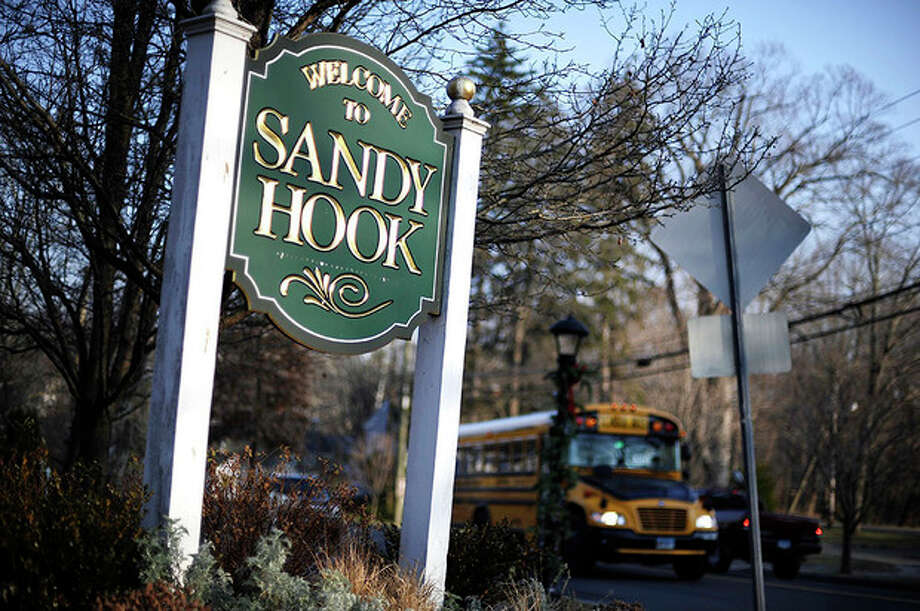 AP Photo / Jessica HillA bus drives past a sign reading Welcome to Sandy Hook Wednesday. The 911 calls from the Sandy Hook Elementary School shootings released show town dispatchers urged panicked callers to take cover, mobilized help and asked about the welfare of the children as the boom of gunfire could be heard at times in the background. The recordings are released under court order after a legal challenge from The Associated Press. / FR125654 AP