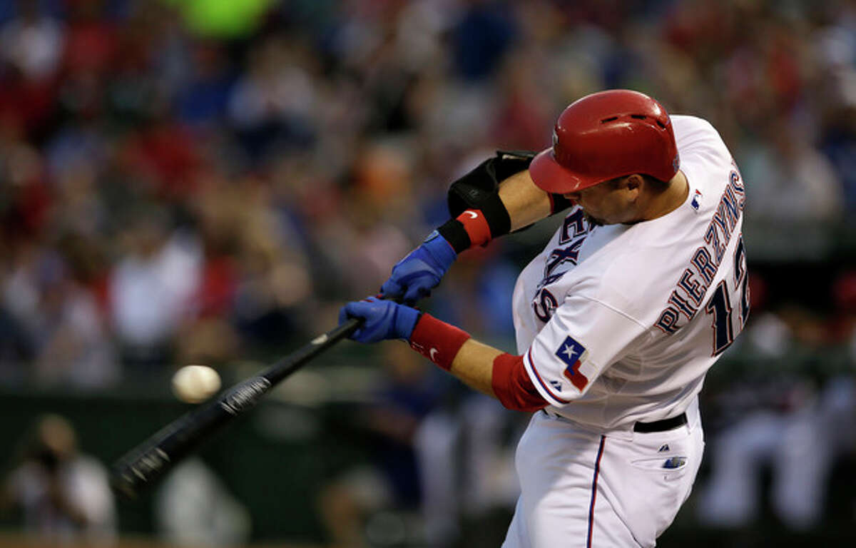 FILE - In this Sept. 13, 2013 file photo, Texas Rangers' A.J. Pierzynski swings at a pitch in the first inning of a baseball game against the Oakland Athletics, in Arlington, Texas. A person with knowledge of the negotiations says free-agent catcher Pierzynski is closing in on a one-year contract with the Boston Red Sox. The deal would be pending a physical. The person spoke on condition of anonymity Tuesday, Dec. 3, 2013, because the team hadn't finalized the agreement. (AP Photo/Tony Gutierrez, File)