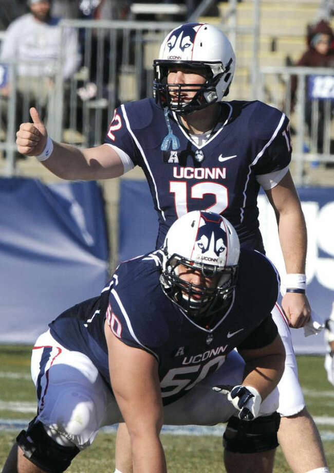 AP photoConnecticut quarterback Casey Cochran (12) signals while guard Tyler Bullock (50) looks on during the first half of Saturday's game against Rutgers at Rentschler Field. Almost forgotten for a year-and-a-half, Cochran has taken over as UConn's starter and led the Huskies to a pair of victories.