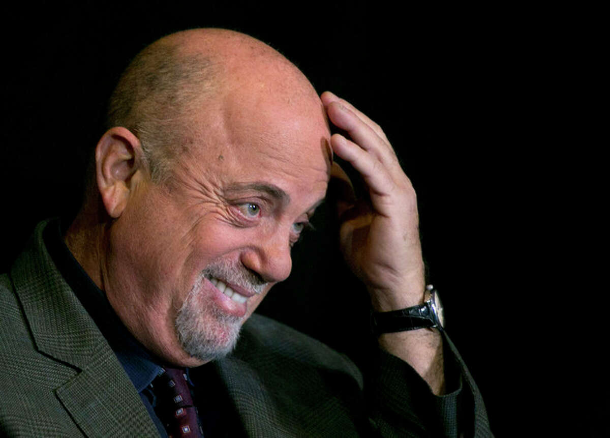 Billy Joel smiles during news conference at Madison Square Garden, Tuesday, Dec. 3, 2013 in New York. The icon announced he will perform a residency at the famed NYC venue once a month for as many months as New Yorkers demand. He is set to perform sold out shows on Jan. 27, Feb. 3, March 21 and April 28. He will also perform on his 65th birthday, which is May 9. (AP Photo/Mark Lennihan)