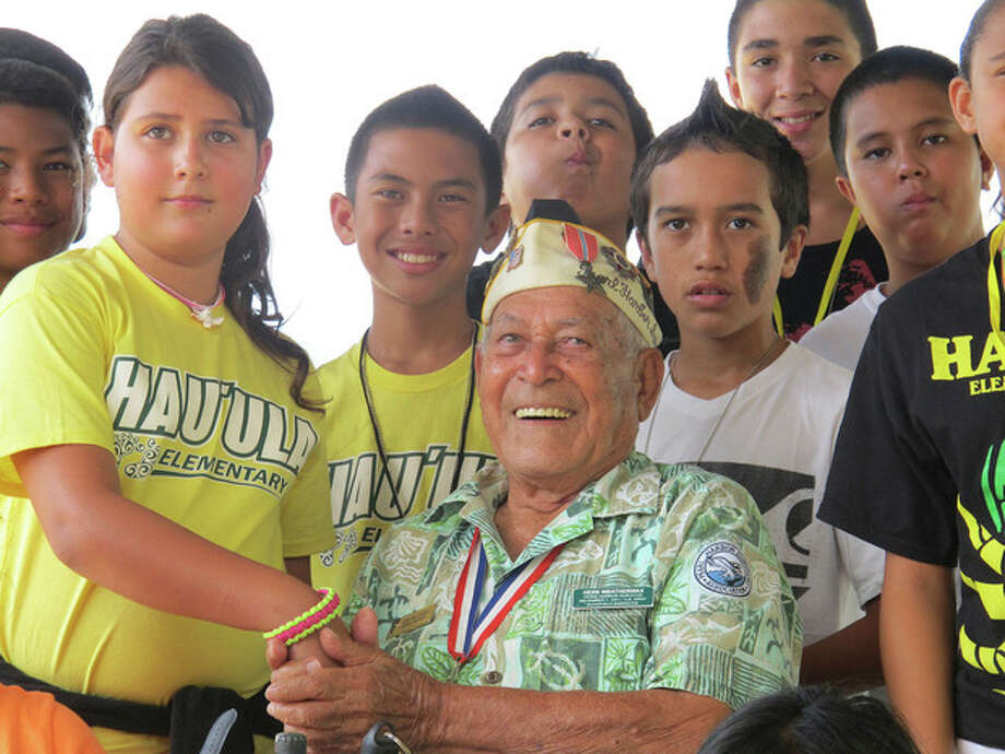 In this photo taken Nov. 22, 2013, Herb Weatherwax, seated, poses for a photo with Hauula Elementary School sixth graders from left Dawson Langinbelik, Rachel Cheney, Frank Kojima, La'a Beatty, Chase Colleado, Makoa Ahquin-Soren and Keola Baily in Pearl Harbor, Hawaii. The 96-year-old retired electrician is one of four Pearl Harbor survivors who volunteers to greet visitors at the historic site. On Saturday is the 72nd anniversary of the 1941 attack by Japan on Pearl Harbor. (AP Photo/Audrey McAvoy) / AP