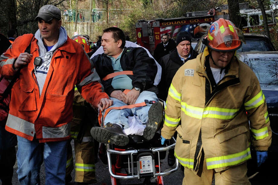 FILE - In this file photo taken on Sunday, Dec. 1, 2013, Metro North Railroad engineer William Rockefeller is wheeled on a stretcher away from the area where the commuter train he was operating derailed in the Bronx borough of New York. The engineer driving the commuter train that went off the rails in New York City last weekend has been suspended without pay according to a spokesman for Metro-North Railroad Thursday Dec. 5, 2013. (AP Photo/Robert Stolarik, File) / AP