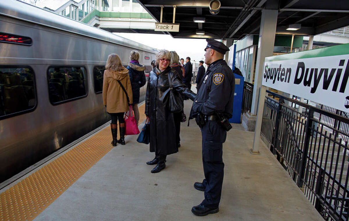 Metro-North customers stand by as a passenger train pulls into the Spuyten Duyvil station in the Bronx borough of New York Wednesday, Dec. 4, 2013, a few hundred feet from where a fatal derailment disrupted service on the Hudson Line of the railroad Sunday, Dec. 1. The line was running at ninety eight percent capacity tWednesday, according to Metro-North. (AP Photo/Craig Ruttle)