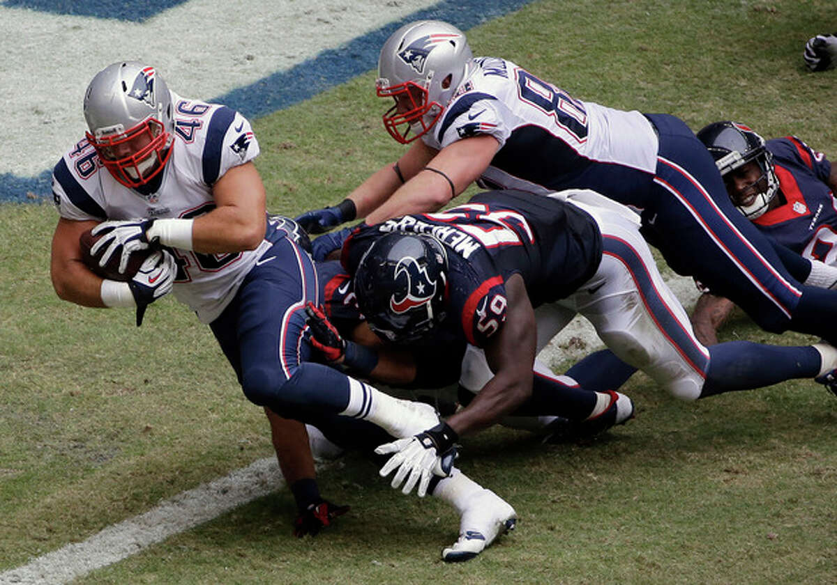 New England Patriots' James Develin (46) scores a touchdown against the Houston Texans during the third quarter of an NFL football game on Sunday, Dec. 1, 2013, in Houston. (AP Photo/David J. Phillip)