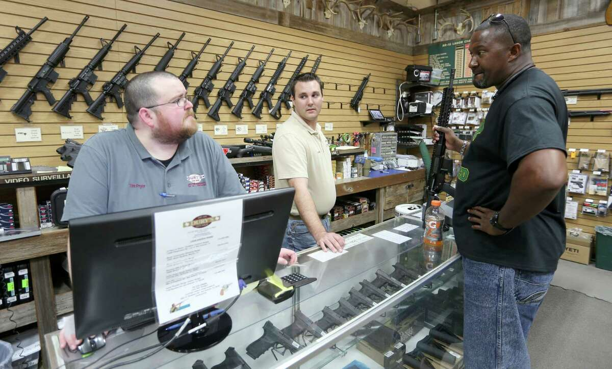Tim Pryor, left, and Ross Kelley-Vincent, center, talk Wednesday June 15, 2016 with regular customer Mardio Lattimore, a retired Army combat medic, at Dury's Gun Shop.