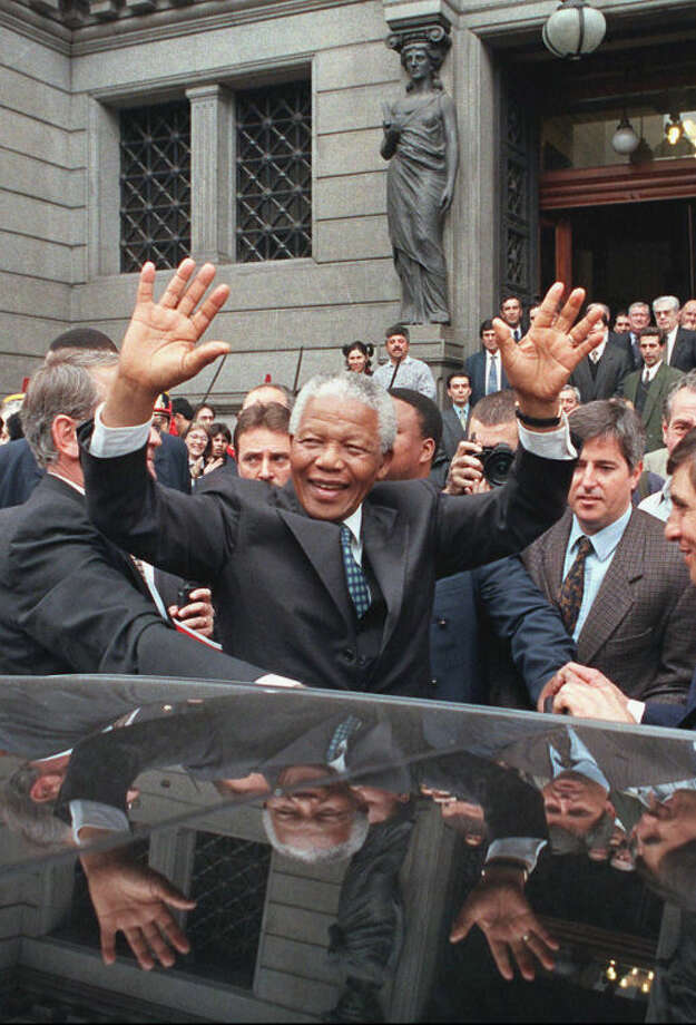 FILE - In this July 23, 1998 file photo, South African President Nelson Mandela greets a crowd outside the National Congress building in Buenos Aires, Argentina, as he arrives for a meeting of the four-nation South American Common Market, or Mercosur. South Africa's president Jacob Zuma says, Thursday, Dec. 5, 2013, that Mandela has died. He was 95. (AP Photo/Daniel Muzio, File)