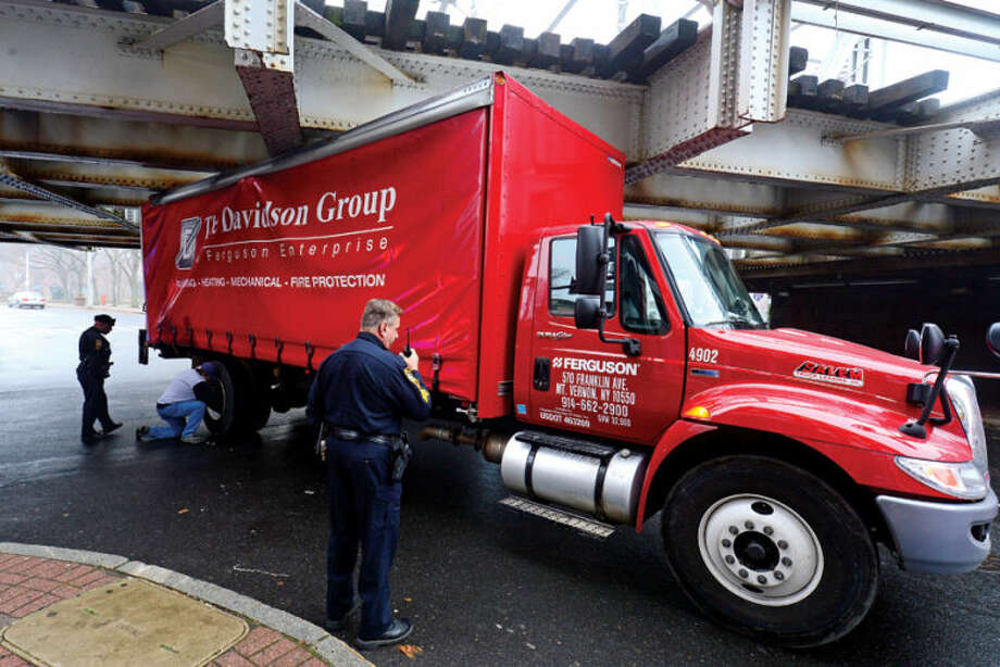 Hour photo / Erik Trautmann A service truck with Ferguson Enterprises of Mt Vernon New York failed to clear the railroad bridge on Washington St becoming stuck and disrupting traffic Thursday.