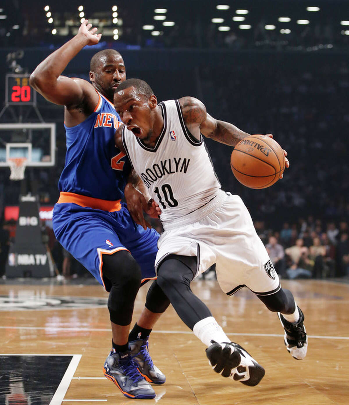 Brooklyn Nets guard Tyshawn Taylor (10) drives past New York Knicks guard Raymond Felton (2) in the first half of their NBA basketball game at the Barclays Center, Thursday, Dec. 5, 2013, in New York. (AP Photo/Kathy Willens)