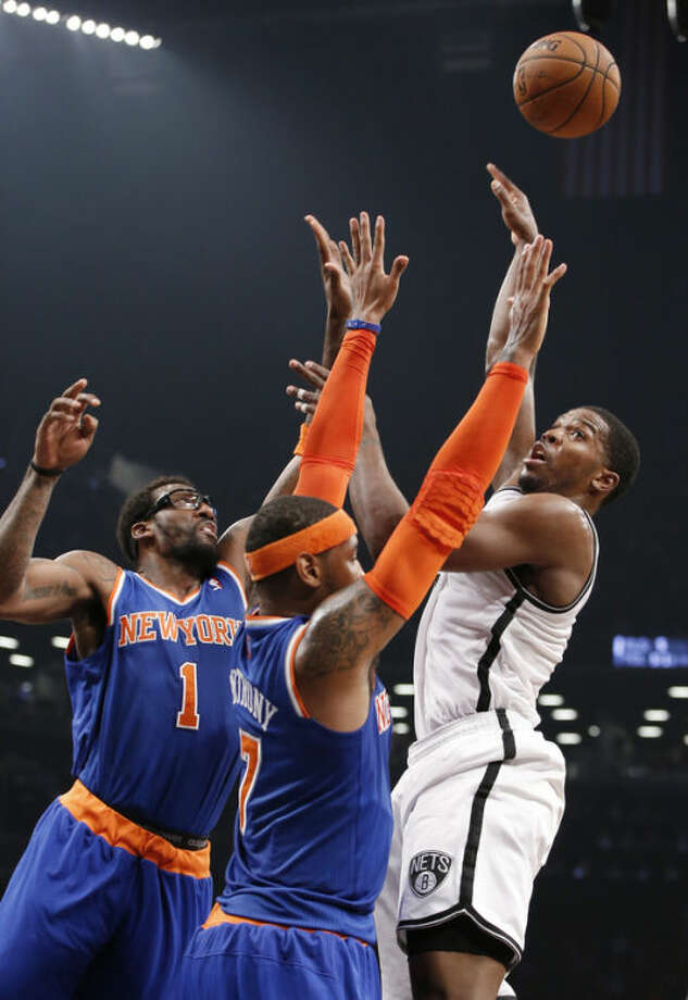 Brooklyn Nets shooting guard Joe Johnson (7) shoots over as New York Knicks forward Amar'e Stoudemire (1) and New York Knicks forward Carmelo Anthony (7) defend in the first half of their NBA basketball game at the Barclays Center, Thursday, Dec. 5, 2013, in New York. (AP Photo/Kathy Willens)