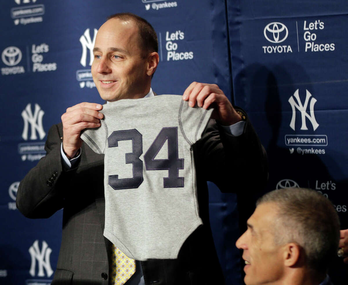 New York Yankees general manager Brian Cashman, left, presents baby clothes to Brian McCann for his young children during a baseball news conference at Yankee Stadium in New York, Thursday, Dec. 5, 2013. McCann, an all-Star catcher, completed his $85 million, five-year contract with the Yankees on Tuesday, in what the team called a