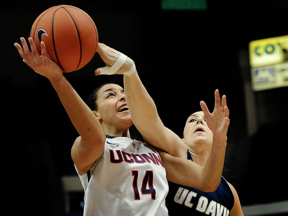 UC Davis' Alyson Doherty, right, fouls Connecticut's Bria Hartley during the first half of an NCAA college basketball game, Thursday, Dec. 5, 2013, in Hartford, Conn. (AP Photo/Jessica Hill) / FR125654 AP