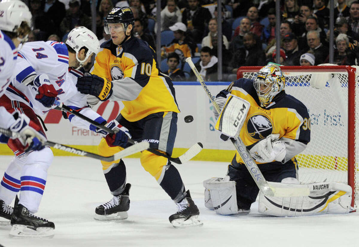 New York Rangers' Taylor Pyatt (14) chases a rebound as Buffalo Sabres' Christian Ehrhoff (10) and Ryan Miller (30) defend during the second period of an NHL hockey game in Buffalo, N.Y., Thursday, Dec. 5, 2013. (AP Photo/Gary Wiepert)
