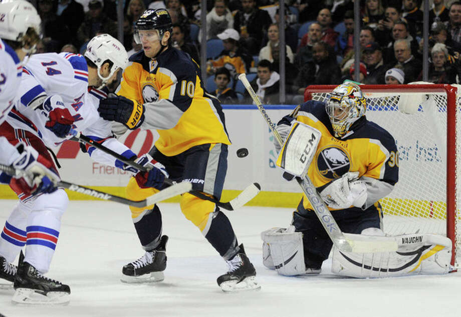 New York Rangers' Taylor Pyatt (14) chases a rebound as Buffalo Sabres' Christian Ehrhoff (10) and Ryan Miller (30) defend during the second period of an NHL hockey game in Buffalo, N.Y., Thursday, Dec. 5, 2013. (AP Photo/Gary Wiepert) / FR170498 AP