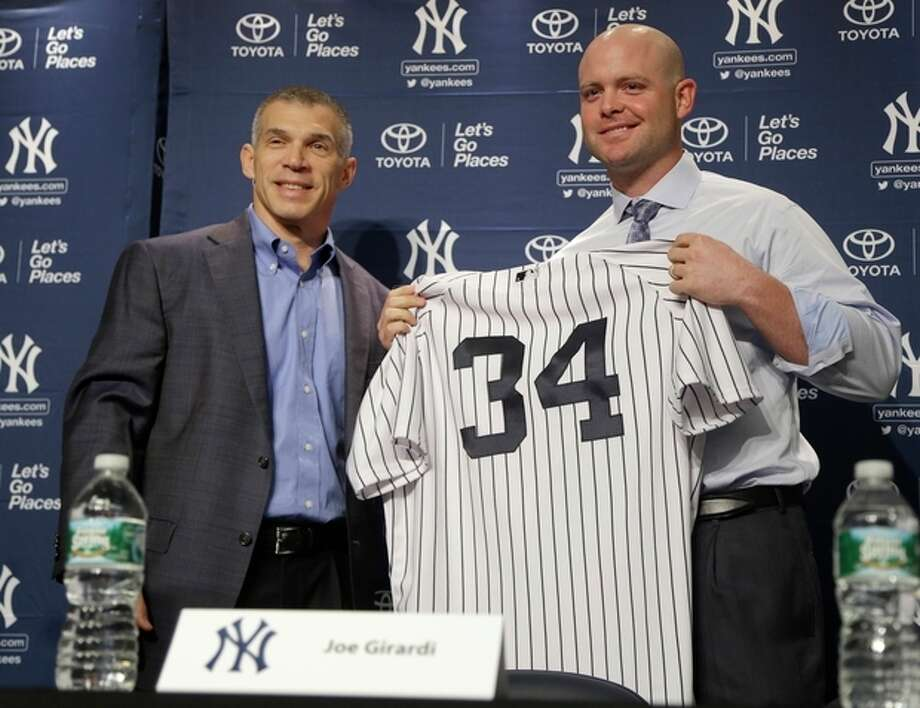 New York Yankees' Brian McCann, right, poses for a picture with his new uniform and manager Joe Girardi at a news conference where he was introduced at Yankee Stadium in New York, Thursday, Dec. 5, 2013. (AP Photo/Seth Wenig) / AP