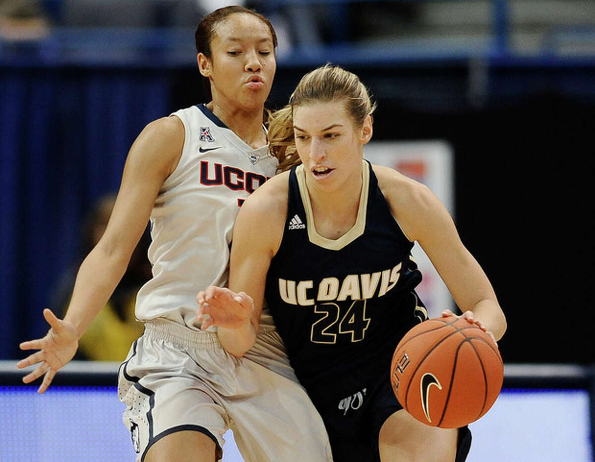 UC Davis' Brianna Salvatore drives around Connecticut's Saniya Chong during the first half of an NCAA college basketball game, Thursday, Dec. 5, 2013, in Hartford, Conn. (AP Photo/Jessica Hill)