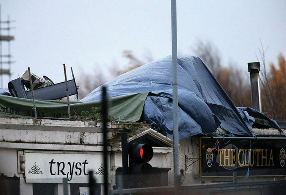 AP Photo / Scott HeppellPart of the helicopter tail fin and rotor is seen after the wind has blown off the sheet covering the scene on Saturday, following the helicopter crash at the Clutha Bar in Glasgow, Scotland. Scottish emergency workers were sifting through wreckage for survivors of a police helicopter crash onto a crowded Glasgow pub that has killed at least one person and injured more than two dozen. The Clutha pub, near the banks of the River Clyde, was packed Friday night and a ska band was in full swing when the chopper slammed through the roof. The number of fatalities is expected to rise, officials said. / AP