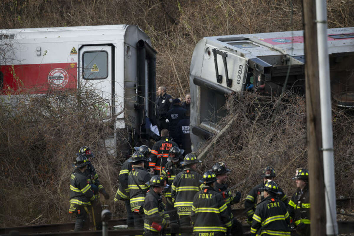 Emergency personnel gather at the scene of the derailment of a Metro-North passenger train in the Bronx borough of New York Sunday, Dec. 1, 2013. The train derailed on a curved section of track in the Bronx on Sunday morning, coming to rest just inches from the water and causing multiple fatalities and dozens of injuries, authorities said. Metropolitan Transportation Authority police say the train derailed near the Spuyten Duyvil station. (AP Photo/Craig Ruttle)
