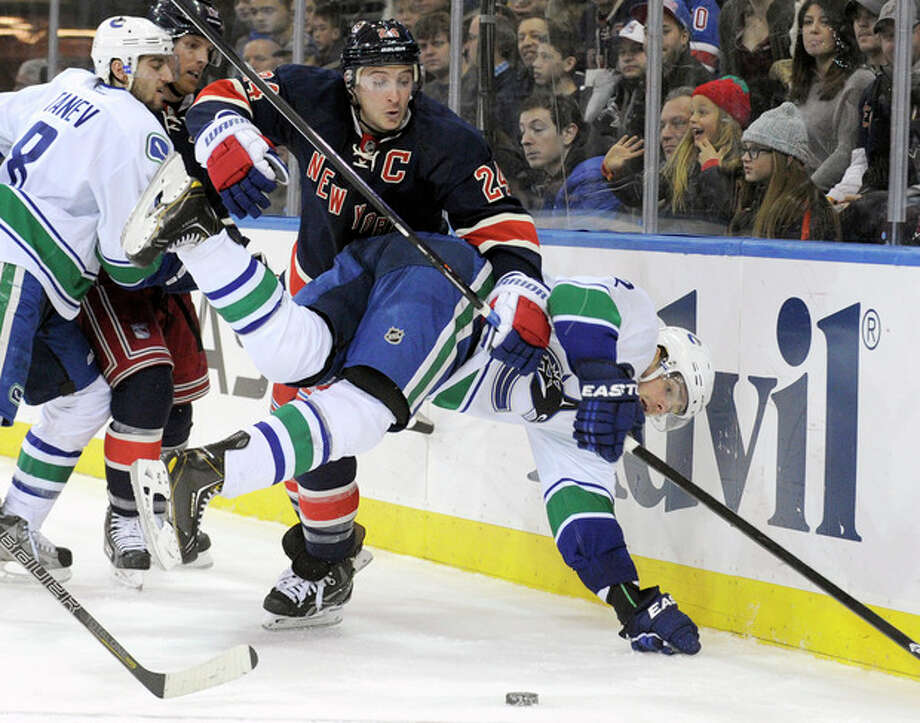 New York Rangers' Ryan Callahan (24) checks Vancouver Canucks' Dan Hamhuis during the second period of an NHL hockey game Saturday, Nov. 30, 2013, at Madison Square Garden in New York. (AP Photo/Bill Kostroun) / FR51951 AP