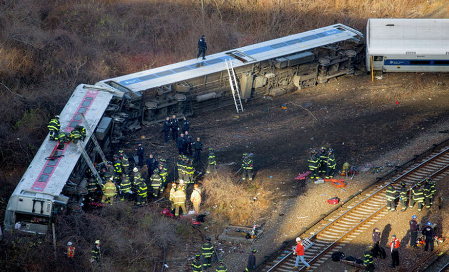 First responders gather at the derailment of a Metro-North passenger train in the Bronx borough of New York Sunday, Dec. 1, 2013. derailed on a curved section of track in the Bronx on Sunday morning, coming to rest just inches from the water and causing multiple fatalities and dozens of injuries, authorities said. Metropolitan Transportation Authority police say the train derailed near the Spuyten Duyvil station. (AP Photo/Craig Ruttle) / FR61802 AP