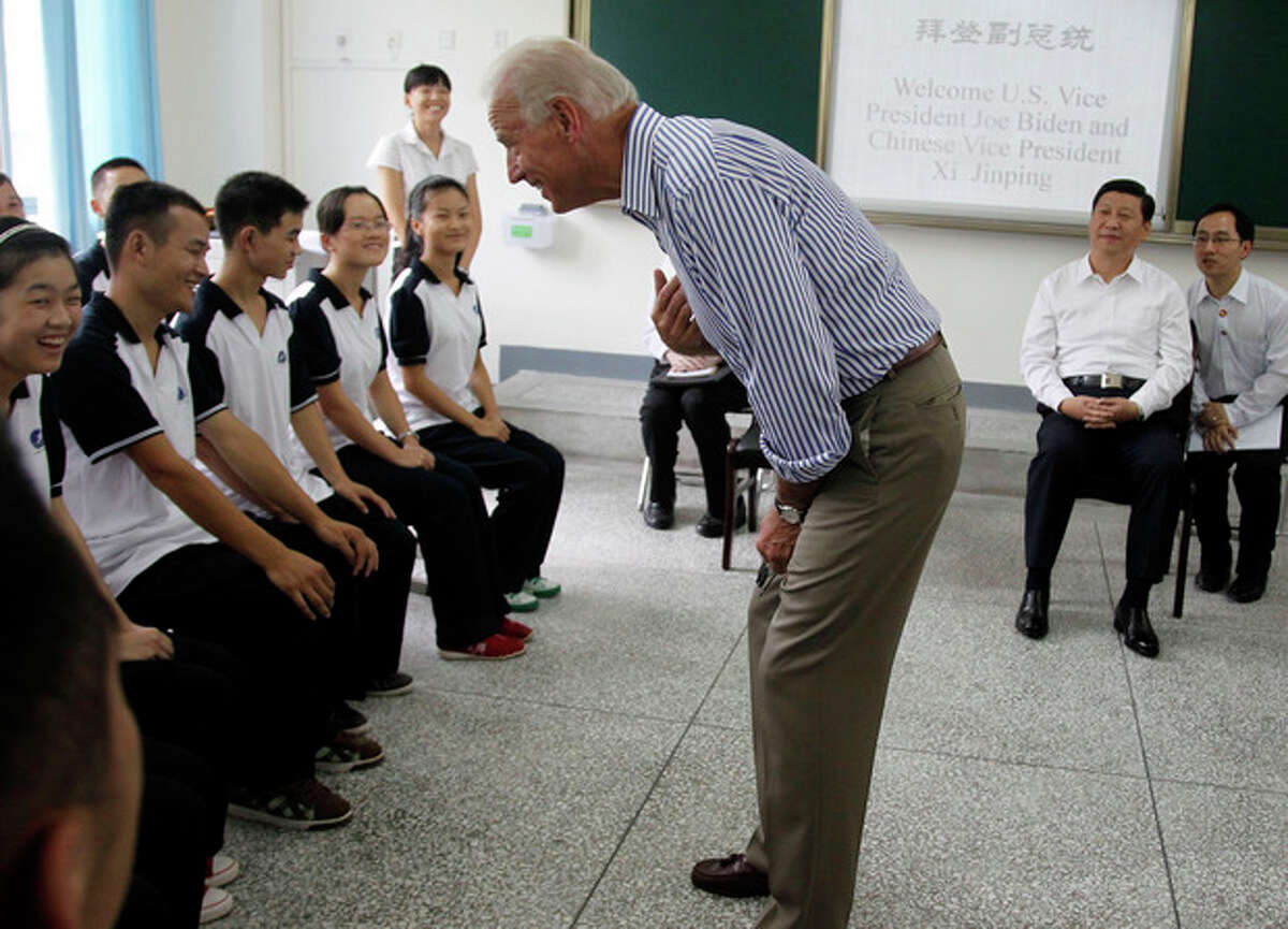 Ap photo In this Aug. 21, 2011, file photo. U.S. Vice President Joe Biden, center, talks to students as Chinese Vice President Xi Jinping, second from right, watches during their visit to the Qingchengshan High School in Dujiangyan in southwestern China's Sichuan province, Sunday, Aug. 21, 2011.