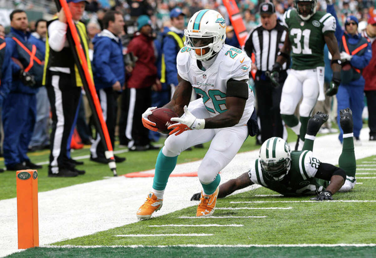 Miami Dolphins running back Lamar Miller (26) steps out of bounds after being hit by New York Jets defensive back Aaron Berry (22) before the goal line during the first half of an NFL football game, Sunday, Dec. 1, 2013, in East Rutherford, N.J. (AP Photo/Seth Wenig)