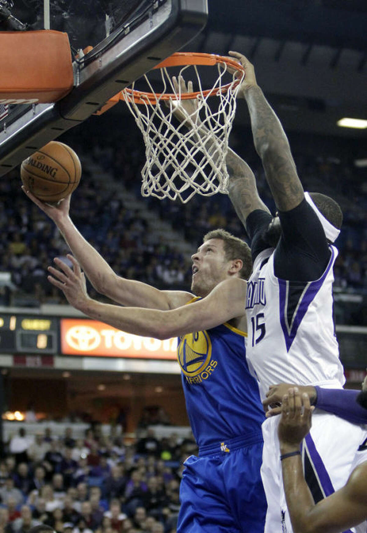 Golden State Warriors forward David Lee, left, goes to the basket against Sacramento Kings center DeMarcus Cousins during the first quarter of an NBA basketball game in Sacramento, Calif., Sunday, Dec. 1, 2013. (AP Photo/Rich Pedroncelli)