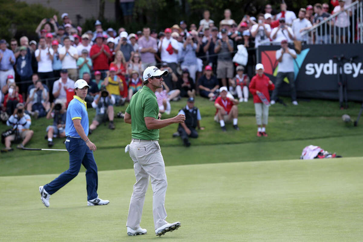 Australia's Adam Scott reacts after sinking a birdie putt on the 18th green as playing partner Rory McIlroy,left, of Northern Ireland looks on during their third round at the Australian Open Golf tournament in Sydney, Australia, Saturday, Nov. 30, 2013.(AP Photo/Rob Griffith)
