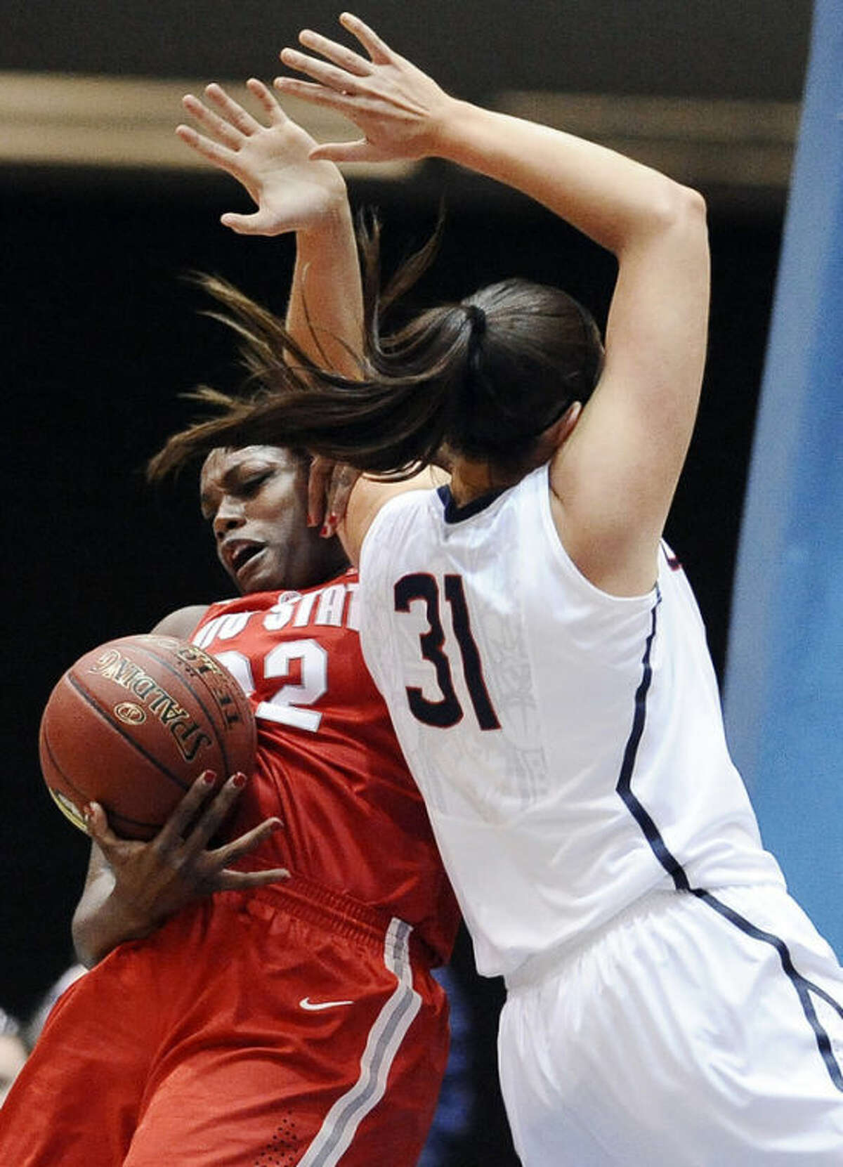 Ohio State's Darryce Moore, left, tangles with Connecticut's Stefanie Dolson, right, as they battle for a rebound during the first half of an NCAA college basketball game Sunday, Dec. 1, 2013, in Springfield, Mass. (AP Photo/Jessica Hill)