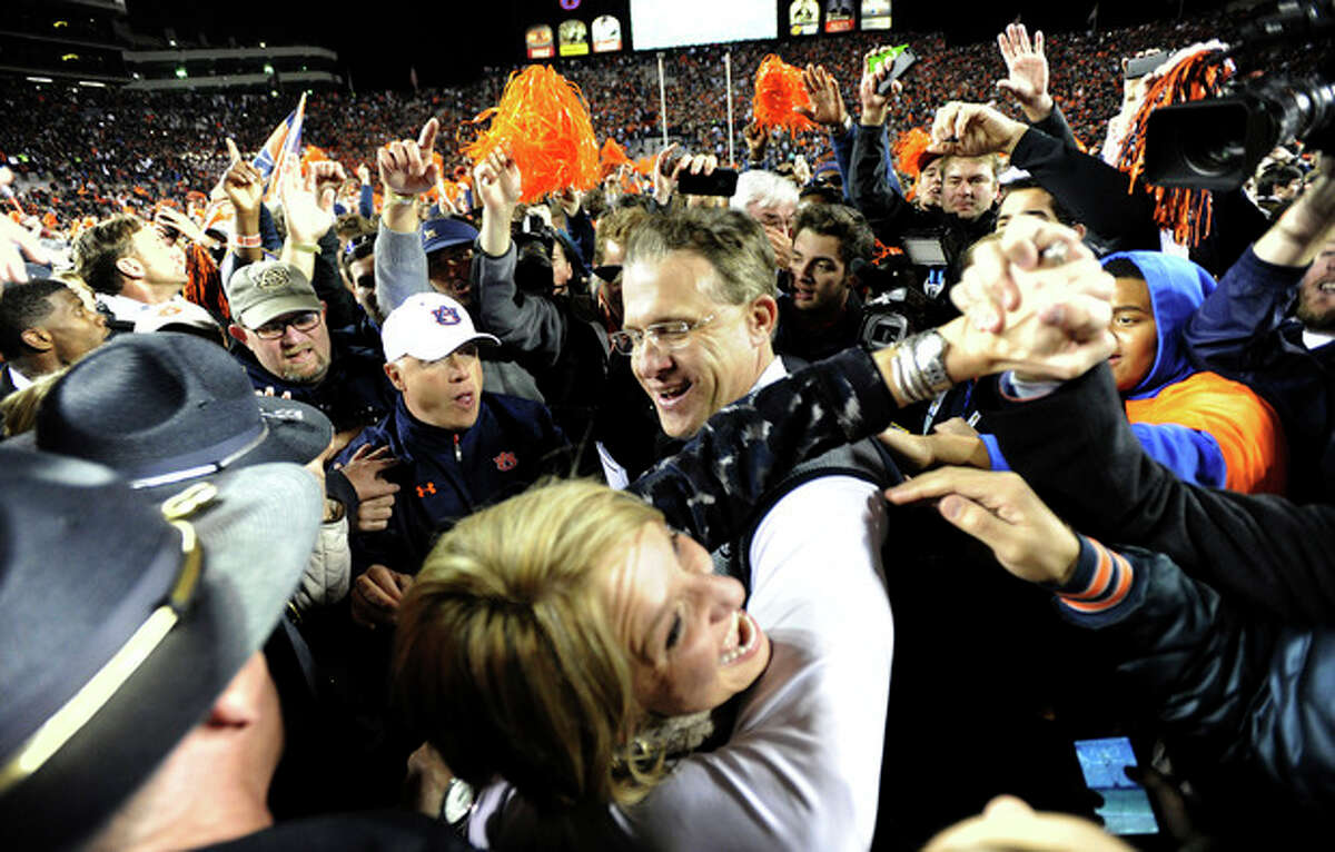 Auburn head coach Gus Malzahn celebrates with his wife Kristi after their 34-28 win over No. 1 Alabama in an NCAA college football game, Saturday, Nov. 30, 2013, at Jordan-Hare Stadium in Auburn, Ala. (AP Photo/AL.com, Julie Bennett) MAGS OUT