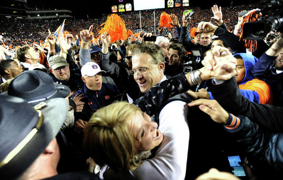 Auburn head coach Gus Malzahn celebrates with his wife Kristi after their 34-28 win over No. 1 Alabama in an NCAA college football game, Saturday, Nov. 30, 2013, at Jordan-Hare Stadium in Auburn, Ala. (AP Photo/AL.com, Julie Bennett) MAGS OUT / AL.COM