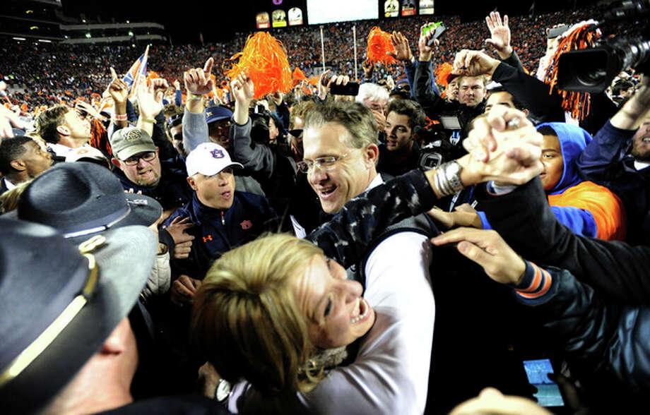 Auburn head coach Gus Malzahn celebrates with his wife Kristi after their 34-28 win over No. 1 Alabama in an NCAA college football game, Saturday, Nov. 30, 2013, at Jordan-Hare Stadium in Auburn, Ala. (AP Photo/AL.com, Julie Bennett) MAGS OUT / AL.COM