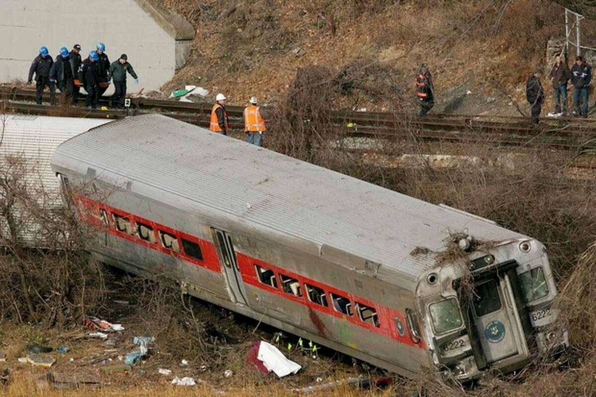 Emergency rescue personnel, top left, remove the body of a victim from the site of a train derailment, Sunday, Dec. 1, 2013 in the Bronx borough of New York. (AP Photo/Mark Lennihan)