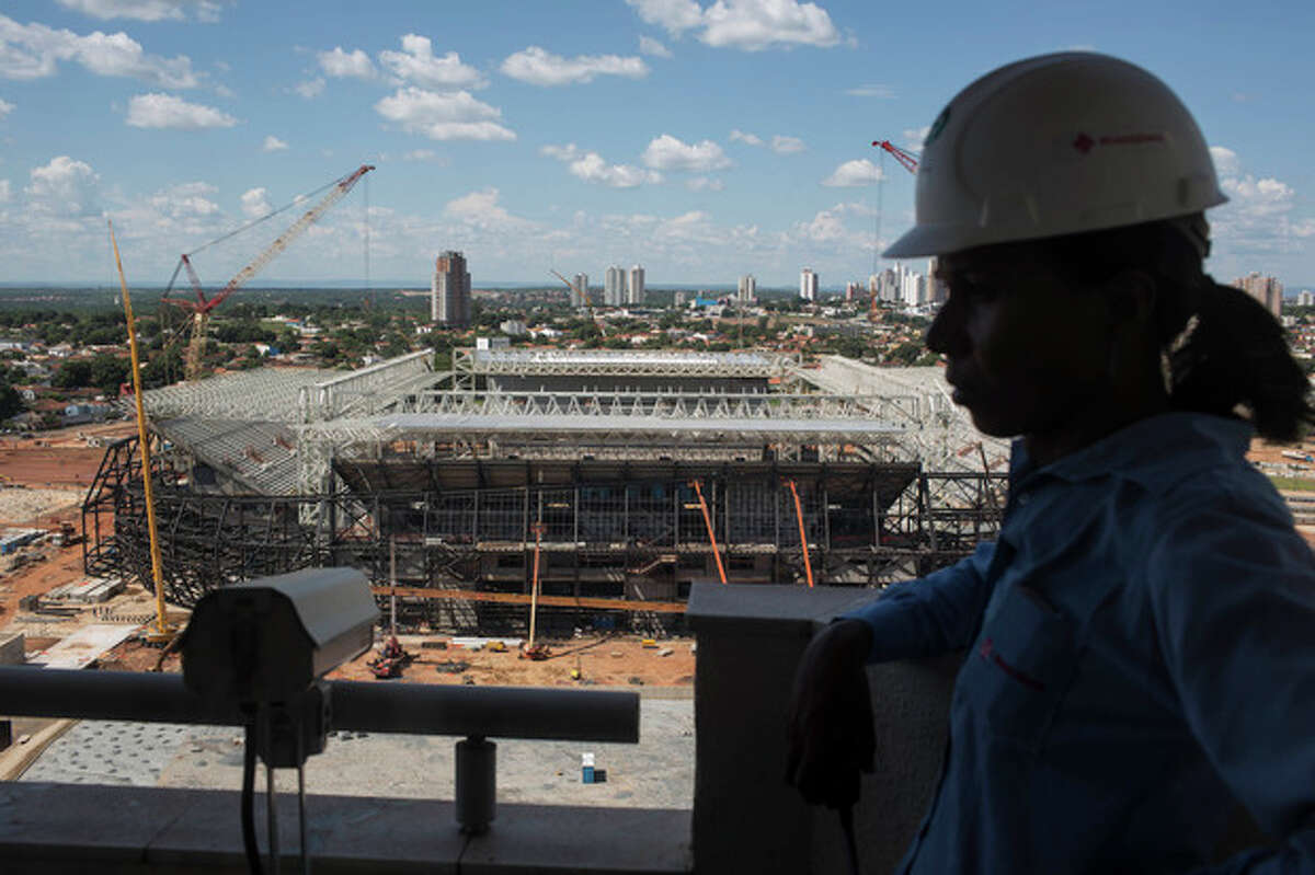FILE .- In this Thursday Nov. 14, 2013 file photo, a worker stands next to a camera used to monitor the construction of the Arena Pantanal stadium that will host games during the 2014 World Cup soccer tournament in Cuiaba, Brazil. There is an ongoing court battle over the supplier of seats for the Arena Pantanal, meaning at any moment a judge can stop construction. From the moment a crane dramatically collapsed at the Sao Paulo stadium, it was clear World Cup organizers would have their hands full trying to deliver all 12 venues by FIFA's end-of-December deadline.(AP Photo/Felipe Dana, File)