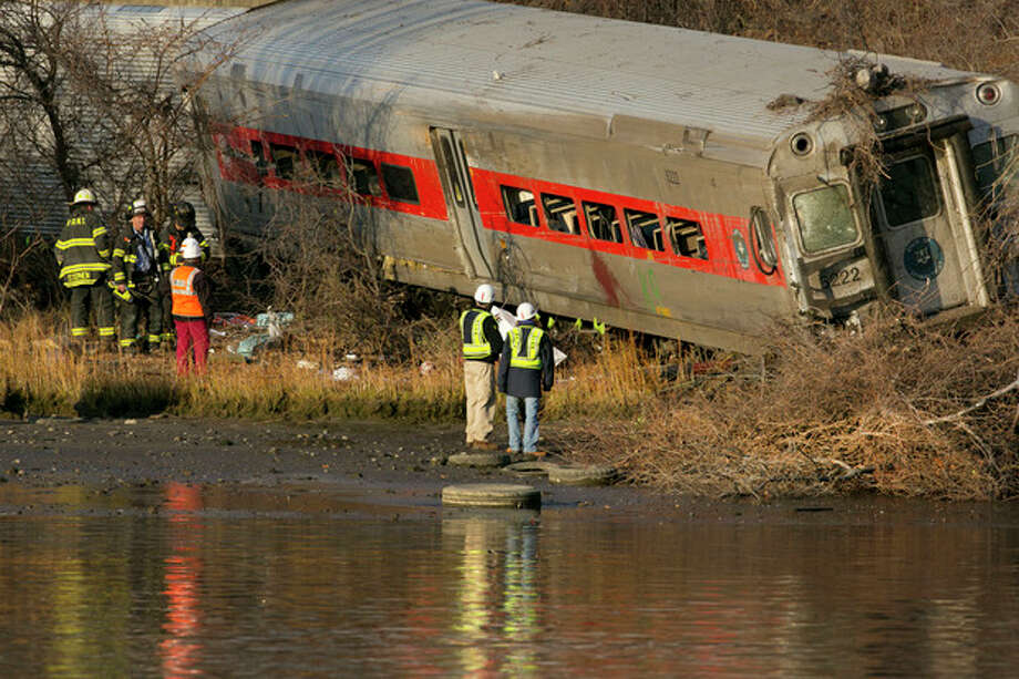 Officials with the National Transportation Safety Board inspect a derailed Metro North commuter train where it almost fell into the Harlem River, Sunday, Dec. 1, 2013 in the Bronx borough of New York. The Metro-North train derailed on a curved section of track early Sunday, coming to rest just inches from the water, killing at least four people and injuring more than 60, authorities said. (AP Photo/Mark Lennihan) / AP