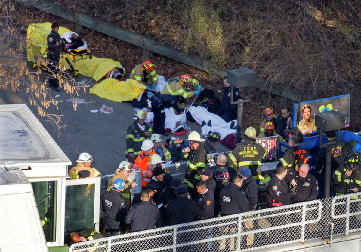 Injured people are tended to by first responders near the site of the derailment of a Metro-North passenger train in the Bronx borough of New York, Sunday, Dec. 1, 2013. The train derailed on a curved section of track in the Bronx on Sunday morning, coming to rest just inches from the water and causing multiple fatalities and dozens of injuries, authorities said. Metropolitan Transportation Authority police say the train derailed near the Spuyten Duyvil station. (AP Photo/Craig Ruttle)